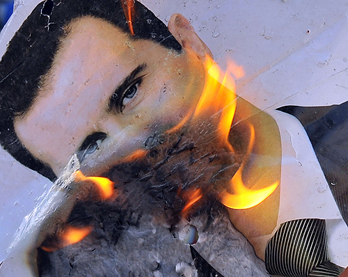 Burning photo of Syrian President Bashar al-Assad