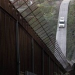 A Border Patrol cruiser drives along the fence between Arizona and Mexico.