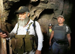 "Autodefensas spokesperson Estanislao Beltran and police search caves in Arteaga for at-large Caballeros Templarios leader Servando Gomez Martinez, ""La Tuta."""
